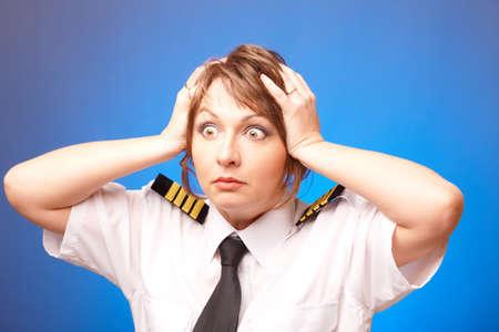 femme inqui�te: Worried femme pilote en uniforme avec epauletes l'avenir, debout sur fond bleu