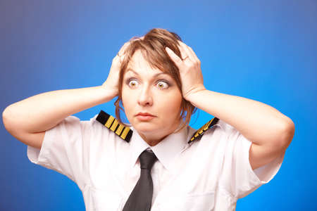 airline uniform: Worried woman pilot wearing uniform with epauletes looking ahead, standing on blue background