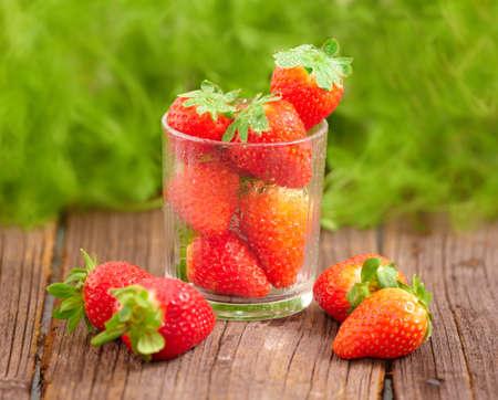 Fresh strawberries in garden on wooden board photo