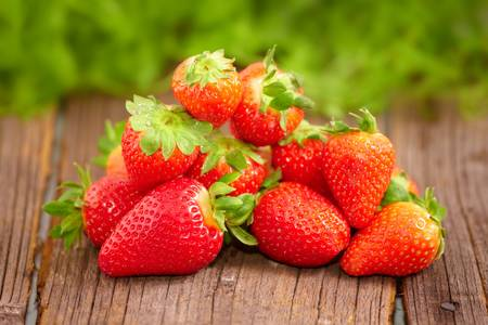 Fresh strawberries in garden on wooden board photo