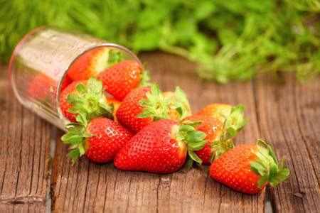Fresh strawberries in glass on wooden board photo