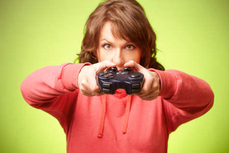 Beautiful womanl with gamepad playing vieogame over green background  Focus on gamepad photo