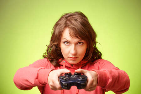 Beautiful womanl with gamepad playing vieogame over green background  Focus on face photo