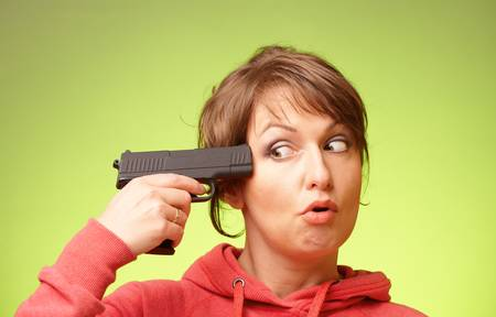 Woman with pistol pointing on her head standing over green background photo