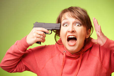 Screaming woman with pistol pointing on her head standing over green background photo
