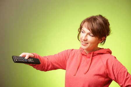 Beautiful woman changing the television channels using a remote controller over green background photo