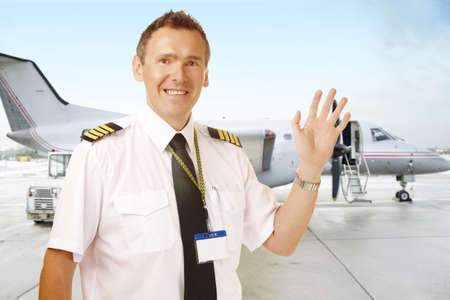 epaulettes: Airline pilot wearing uniform with epaulettes waving, with passenger aircraft in background