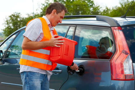 petrol can: Man pouring fuel into the gas tank of his car from a red gas canister