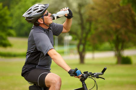 Tired biker resting and drinking from water bottle  photo
