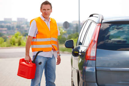 petrol can: Man with gas tank standing near his car