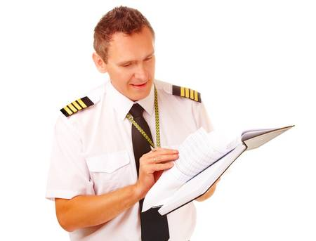 Airline pilot wearing hirt with epaulets and tie filling in and checking papers logbook, weather forecast. Headset on the table.
