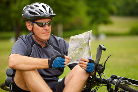 active lifestyle: Man with bike checking map and looking around.