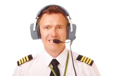 piloto: Piloto de L�nea A�rea en uniforme con charreteras y los auriculares profesionales. Foto de archivo