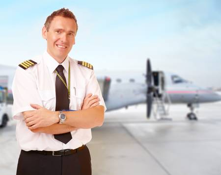 piloto: Piloto de L�nea A�rea en uniforme con charreteras con aviones de pasajeros en el fondo Foto de archivo