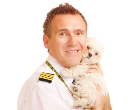 epaulets: Airline pilot wearing uniform with epaulettes with little puppy, dog breed is Maltese.   Stock Photo