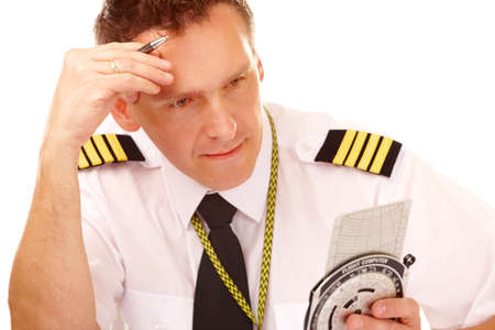epaulets: Airline pilot wearing hirt with epaulets and tie using flight computer for navigation calculations, filling in and checking papers flight plan.