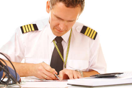 epaulets: Airline pilot wearing hirt with epaulets and tie filling in and checking papers flight plan, weather forecast. Headset on the table.