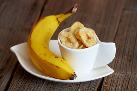 Fried  sliced banana chips with fresh banana  Healthy organic tropical snack  photo