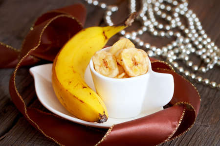 Fried  sliced banana chips with fresh banana  Healthy organic tropical snack  photo