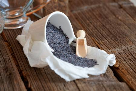 opiate: Dried organic poppy seed on wooden table Stock Photo