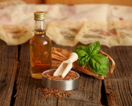 flaxseed: Dried linseed with macerated oil isolated on wooden table