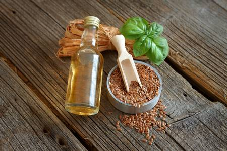 linseed oil: Dried linseed with macerated oil isolated on wooden table