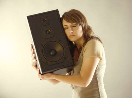 preamp: Young beautiful woman with closed eyes holding big wooden speaker and listening music Stock Photo