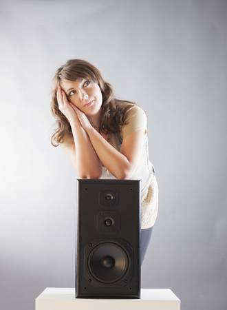 preamp: Young beautiful cheerful woman with hand on the big wooden speaker and listening music