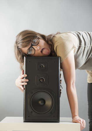 preamp: Young beautiful tired woman with glasses laying on the big wooden speaker and listening music