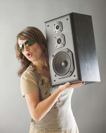 preamp: Young beautiful surprised woman with sunglasses holding big wooden speaker and listening music