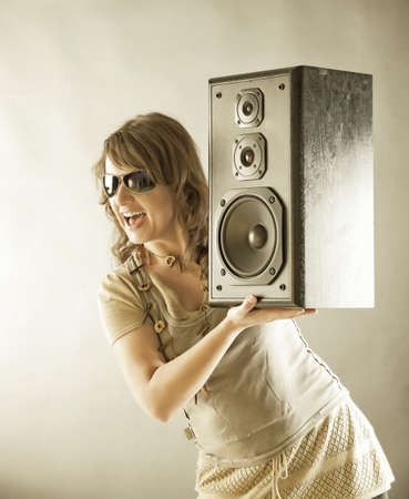 preamp: Young beautiful smiling woman with sunglasses holding big wooden speaker and listening music