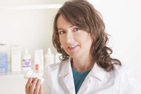 A cheerful young woman pharmacist with a bottle of drugs standing in pharmacy drugstore  photo