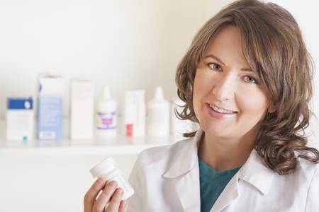 A cheerful young woman pharmacist with a bottle of drugs standing in pharmacy drugstore