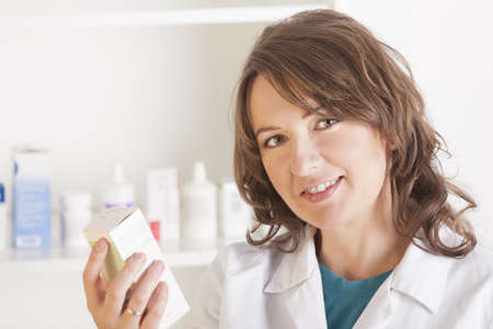 A cheerful young woman pharmacist with a bottle of drugs standing in pharmacy drugstore Stock Photo - 16661261