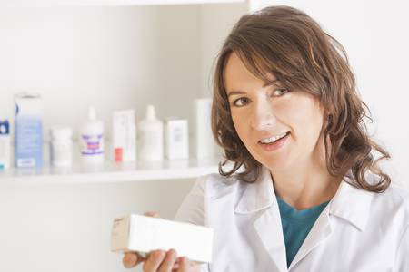 A cheerful young woman pharmacist with a bottle of drugs standing in pharmacy drugstore Stock Photo - 16732407