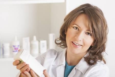 A cheerful young woman pharmacist with a bottle of drugs standing in pharmacy drugstore Stock Photo - 16732404