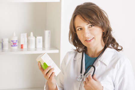 A cheerful young woman pharmacist or a doctor with a stethoscope holding bottle of drugs standing in pharmacy drugstore photo