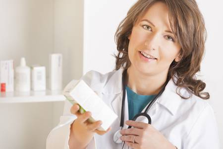 A cheerful young woman pharmacist or a doctor with a stethoscope holding bottle of drugs standing in pharmacy drugstore