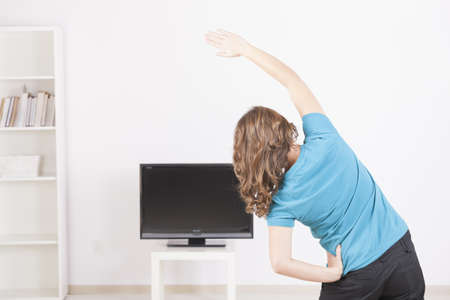 Woman doing fitness at home using on screen TV instructions photo