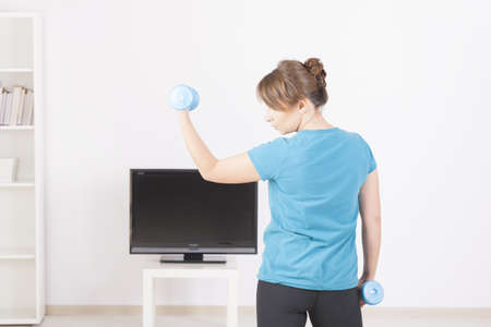 Woman doing fitness with dumb-bells at home using on screen TV instructions photo