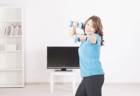 Mujer que hace el gimnasio en casa con pesas de gimnasia con las instrucciones en la pantalla de TV Foto de archivo - 16732392