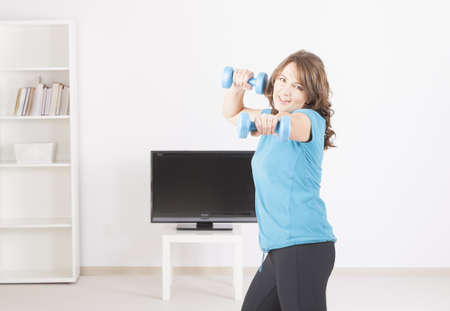 Woman doing fitness at home with dumb-bells using on screen TV instructions photo