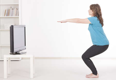 Woman doing fitness at home using on screen TV instructions