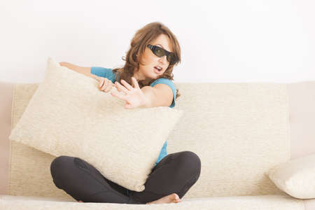 Beautiful young woman watching 3D TV in 3d glasses and hiding behind pillow photo