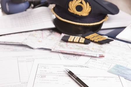 epaulettes: Close up of an airplane pilot equipment including hat, epaulettes and flightplannig papers Stock Photo