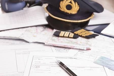 piloto: Primer plano de un equipo piloto de avión, incluido sombrero, charreteras y papeles flightplannig Foto de archivo
