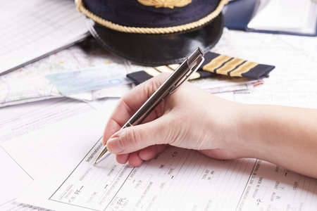 Close up of an airplane pilot hand filling in an flight plan with equipment including hat, epaulettes and other documents in background Stock Photo - 17856267
