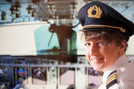 Beautiful woman pilot wearing uniform with epauletes, hat with golden wings sitting inside airliner with visible cockpit during flight  photo
