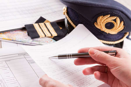 epaulettes: Close up of an airplane pilot hand filling in an flight plan and reading METAR with equipment including hat, epaulettes and other documents in background