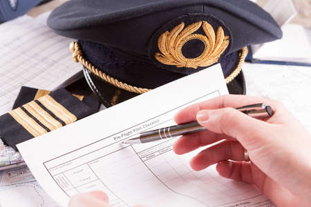 filling in: Close up of an airplane pilot hand filling in an flight plan and pre-flight checklist with equipment including hat, epaulettes and other documents in background Stock Photo